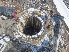 Michels constructed secant compression ring launch and receiving shafts for a microtunneling project. The launch shaft was comprised of 46 intersecting 1-meter-diameter secant piles drilled to a depth of 54 feet. The receiving shaft was comprised of 38 intersecting 1-meter-diameter piles drilled to a depth of 52 feet.