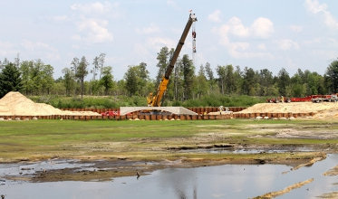 New construction consisted of installation of a pre-cast culvert bridge and associated roadway along with tank trail parallel to the new roadway and reconstruction, contouring and planting of new wetlands.